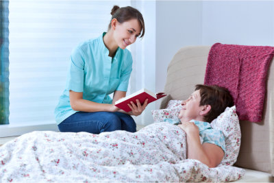 Helpful nurse reading book while patient was lying in bed