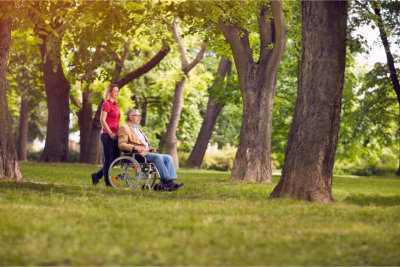 Enjoying senior father in wheelchair and daughter in the park