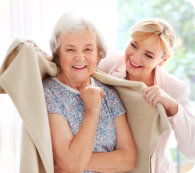 Caregiver covering senior woman with plaid at home