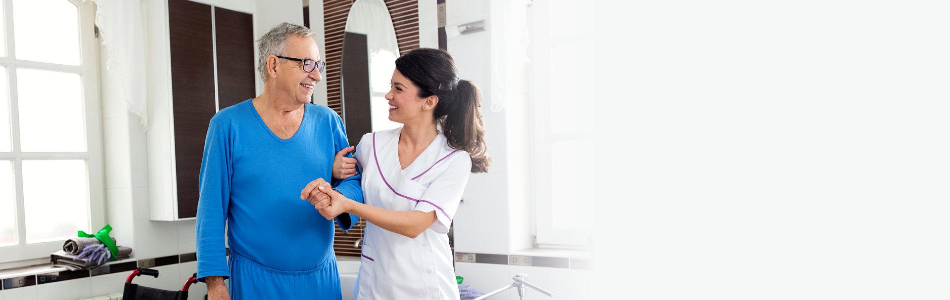 Young beautiful nurse helps senior man at the bathroom