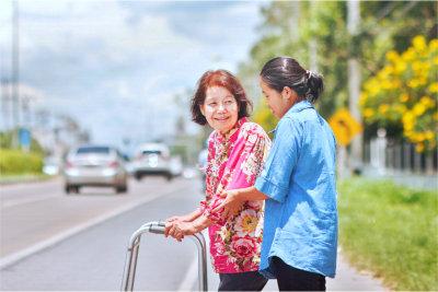 Senior woman using a walker crossing the street